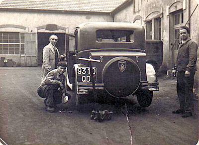 A droite sur la photo à côté de la voiture, mon père mécanicien chez PEUGEOT